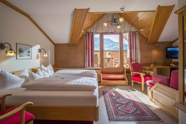 Exklusivzimmer mit gemütlicher Sitzecke rechts und großem Doppelbett, Blick auf Balkon