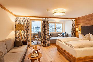 Blick in den Wohnraum der Suite Deluxe mit Bett, Sitzplatz und Panorama-Kuschelecke am Fenster