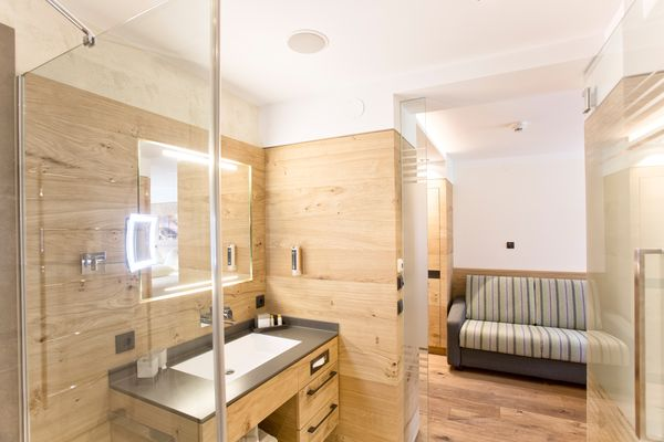 Blick aus dem Badezimmer mit ebenerdiger Dusche Richtung Couch in der Junior Suite des Landhaus