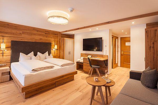 Blick in den Wohnraum der Suite Deluxe mit Bett, Couch und Eingangsbereich