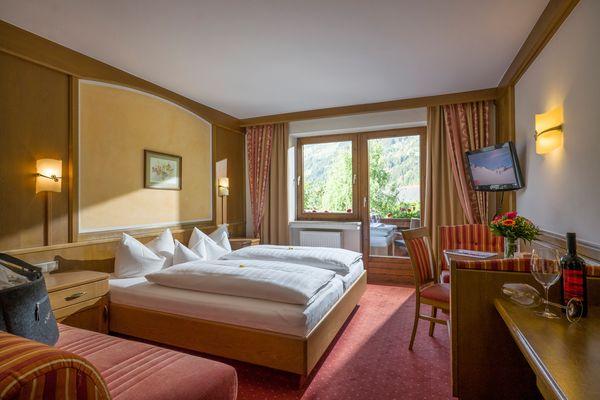 Doppelzimmer mit Blick auf von Couch auf Doppelbett, Schreibtisch, Fensterfront und Balkon