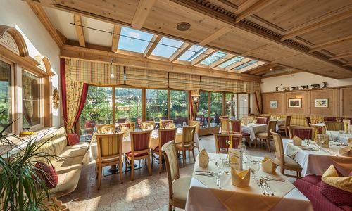 Speisesaal Ferienhotel Sonnenhof, Sonnenlicht kommt strahlt durch Wintergarten auf gedeckte Tische