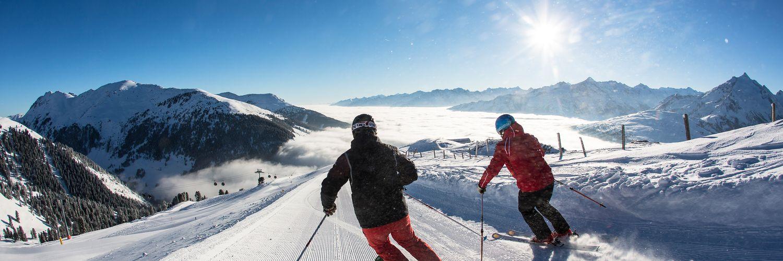 Skifahrer beim Abfahren auf einer sonnigen Piste in der Zillertal Arena