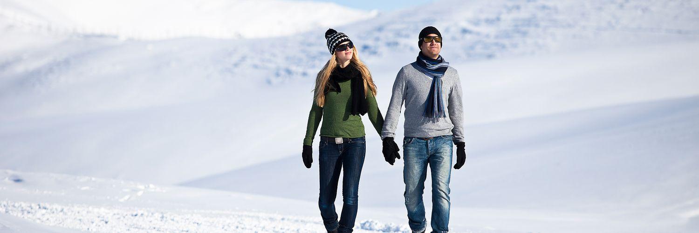 Junges Paar beim Händchen halten während eines romantischen Spazierganges durch die verschneite Winterlandschaft