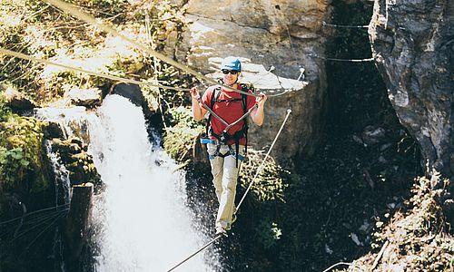 Junger Mann überquert die Seilbrücke am Talbach Klettersteig