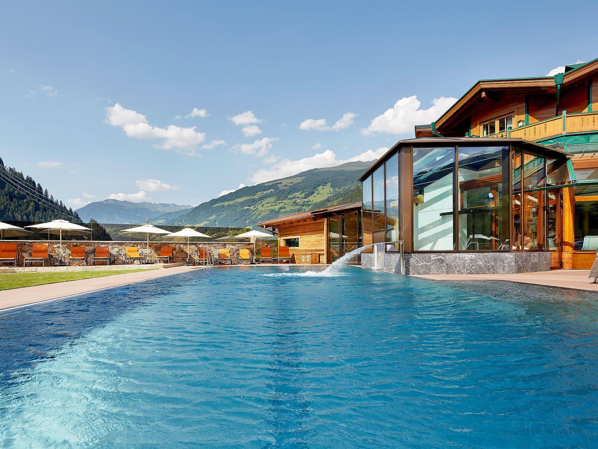 Blick über die Wasserfläche des Freibades auf den Zugang vom Innenbereich und die Sonnenliegen auf der Liegewiese