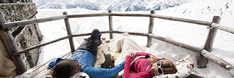 Paar beim Chill-Out auf der Terrasse einer Skihütte, Bergpanorama im Hintergrund