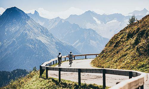 Rückansicht von zwei Mountainbikern beim Weg abwärts der Höhenstraße entlang