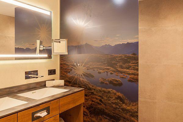 Badezimmer mit begehbarer, ebenerdiger Dusche und Doppelwaschbecken in der Suite Deluxe