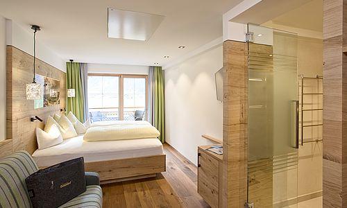 Blick Richtung Bett und Fensterfront in der Junior Suite des Landhauses, Badezimmer rechts