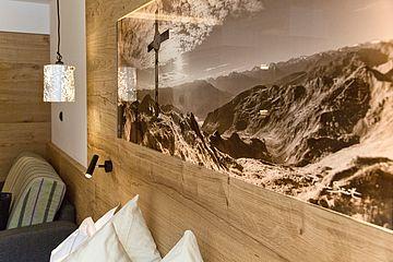Detailaufnahme des hinterleuchteten Bildes im Kopfteil des Doppelbettes der Junior Suite im Landhaus