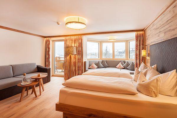 Blick auf das Doppelbett, die Couch und das Panoramafenster mit gemütlicher Sitzecke in der Suite Deluxe