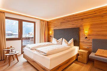 Doppelbett und Holzvertäfelung in der Junior Suite des Ferienhotel Sonnenhof