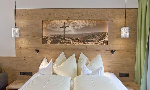 Blick auf das Doppelbett mit Kopfbild in der Comfort Suite des Landhauses