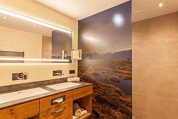 Badezimmer mit Doppelwaschbecken und Motiv-Duschglaswand in der Suite Deluxe