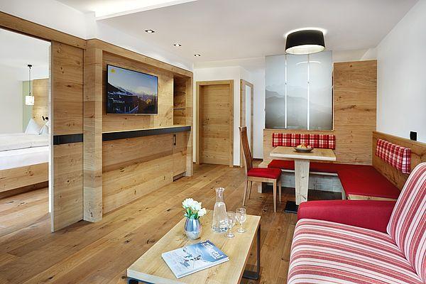 Wohnzimmer mit Eckbank, Couch und an der Wand montiertem Flat-TV in der Superior Suite des Landhauses