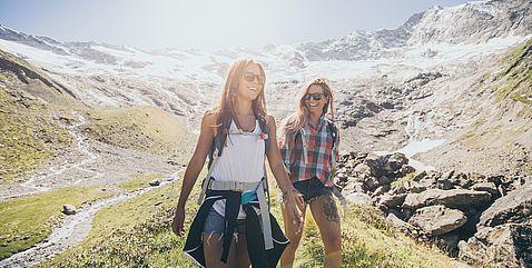Junge Frauen auf dem Weg bergabwärts im Sonnenschein bei einer Bergwanderung