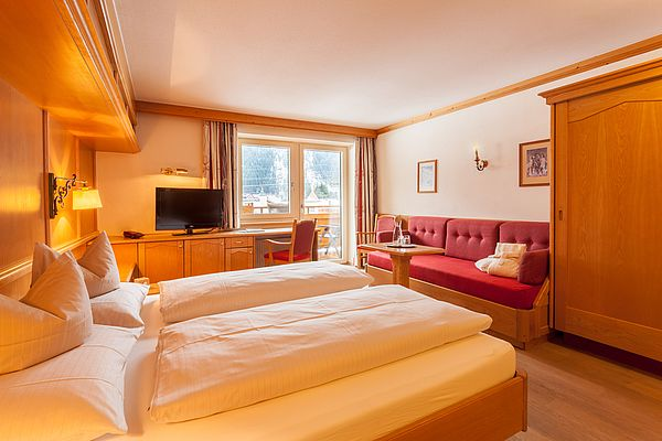 Blick schräg übers Doppelbett auf die Sitzgelegenheit und die Fensterfront im Exklusivzimmer