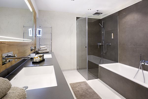 Blick auf den Waschtisch mit Doppelwaschbecken sowie Dusche und Badewanne gegenüber in der Superior Suite des Landhauses