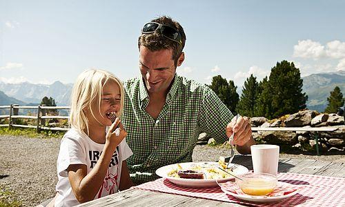 Vater und Tochter essen Kaiserschmarrn auf einer Almhütte mit Bergpanorama im Hintergrund