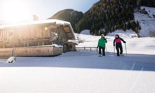 Paar beim Schneeschuhwandern im Schönachtal, links scheint die Sonne ins Bild und auf eine Holzhütte
