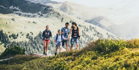 Fröhliche Familie bei einer Bergwanderung im Sonnenschein