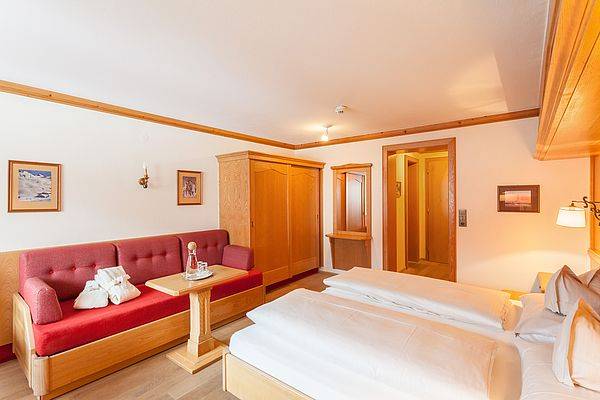 Couch und Doppelbett im Exklusivzimmer des Ferienhotel Sonnenhof