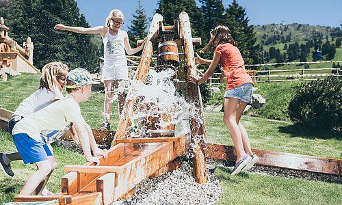 Kids beim Spielen am Wasserrad beim Fichtenschloss in der Zillertal Arena