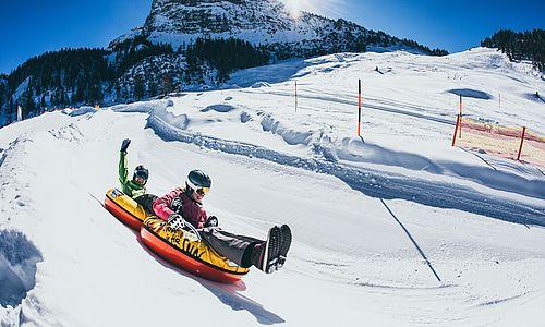 Fröhliche junge Leute beim Snowtubing am Hainzenberg