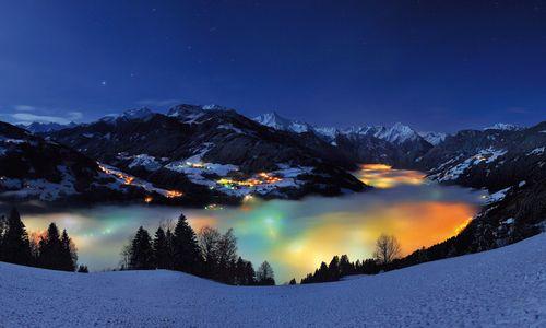 Nachtaufnahme im Winter von Zell am Ziller mit einem Nebelmeer über der beleuchteten Ortschaft, fotografiert von Paul Sürth