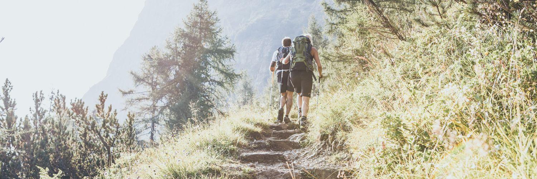 Junges Paar beim Wandern von hinten fotografiert, links scheint die Sonne ins Bild