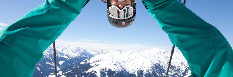 Fotografie des Bergpanoramas durch die Beine einer Skifahrerin hindurch