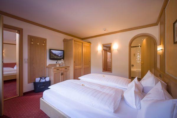 Blick schräg über das Doppelbett im Kleinen Familienzimmer auf angrenzendes Kinderzimmer, Garderobe, Schrankwand und Bad
