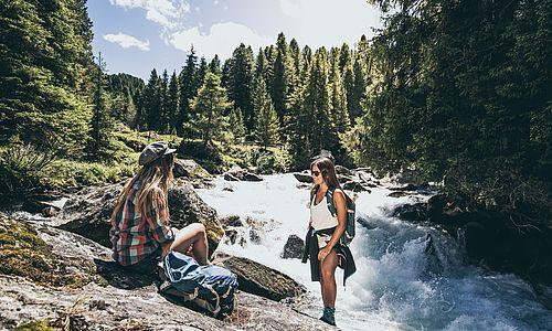 Junge Frauen machen am Wildbach eine Pause während ihrer Bergwanderung