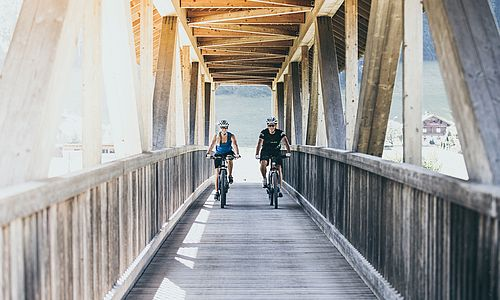 Junges Paar auf Mountainbikes überquert die überdachte Holzbrücke in Laimach
