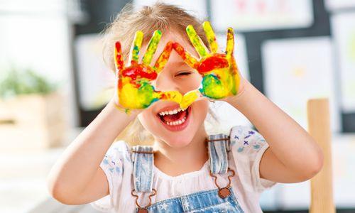 Lachendes Mädchen mit Fingerfarben an den Händen, die sie vors Gesicht hält © jenkoAtaman