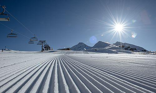 Detailaufnahme einer frisch präparierten Piste mit Skilift im Hintergrund