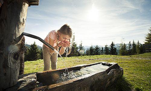 Mädchen trinkt am Brunnen Wasser bei einer Bergwanderung