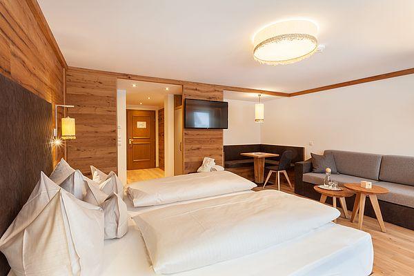 Blick schräg übers Doppelbett der Suite Deluxe auf die Couch und den Eingangsbereich