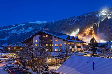 Aussenansicht des Ferienhotel Sonnenhof im Winter, abends, Blick auf beleuchtete Abfahrt Zillertal Arena