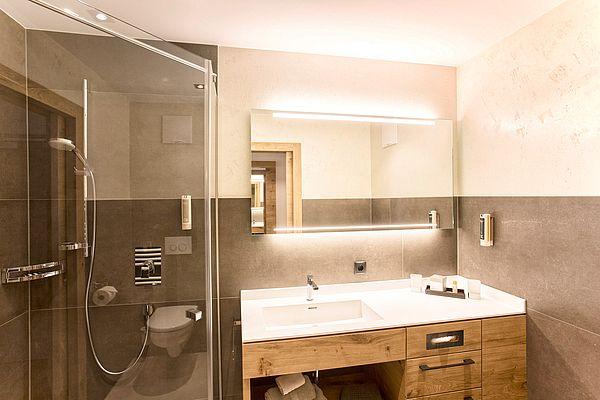 Blick auf Waschtisch und Dusche im Badezimmer des Einzelzimmers im Landhaus