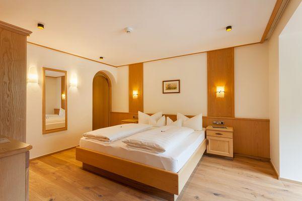 Zimmer mit exklusiver Holzvertäfelung, Doppelbett und Sitzgelegenheit
