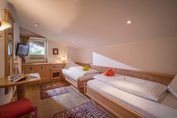 Kinderzimmer mit Dachschräge, Blick auf Einzelbetten, kleinen Schreibtisch und Fenster