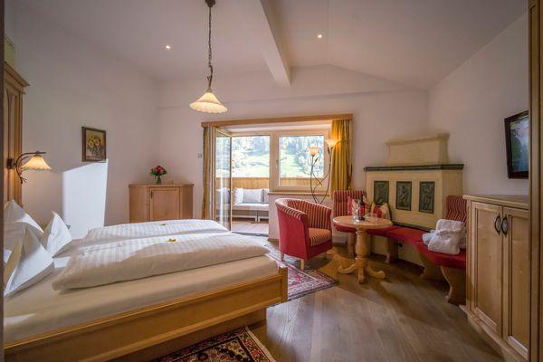 Blick über das Doppelbett auf die gemütliche Sitzecke mit Ofenbank und die einladende Terrasse