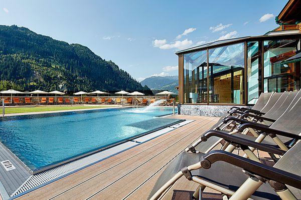 Blick von der Liegefläche am Pool über das Wasserbecken bis hin zur Sonnenwiese