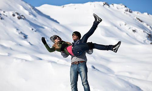 Mann trägt seine Frau auf Händen während eines Spazierganges durch die Winterlandschaft