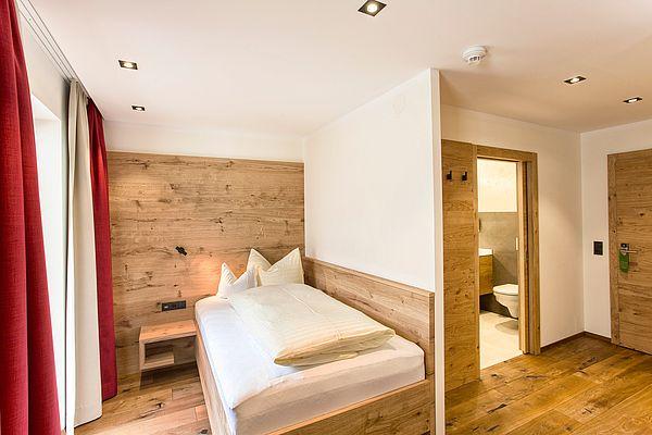 Einzelzimmer im Landhaus, Blick auf Einzelbett und angrenzendes Badezimmer